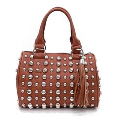 Nothing completes your look like this cognac brown faux leather handbag adorned with large silver studs and a fringed tassel zipper pull. Features soft double handles, fully lined interior, zippered pocket inside, and matching detachable shoulder strap.