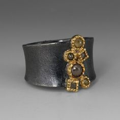 This sculptural Todd Reed ring is perfect for the woman that appreciates handmade, artisan jewelry. The dramatic setting is crafted of oxidized sterling silver, with a grouping of artfully placed rose cut and raw diamonds set in 18k yellow gold. Rose cut diamonds = 0.786ctw, raw diamonds = 0.2ctw @quadrum