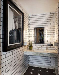 restaurant bathroom with dark-grouted white subway tile and a black and white hex tile floor