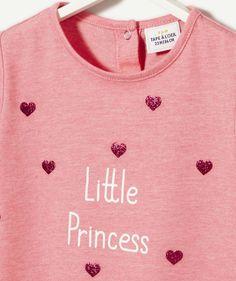 LA BRASSIERE ABEILLE :                     Une brassière pour nos jolies princesses !            LA BRASSIERE ABEILLE, col rond, manches courtes, print et détails sequins devant, 2 boutons pressions au dos,