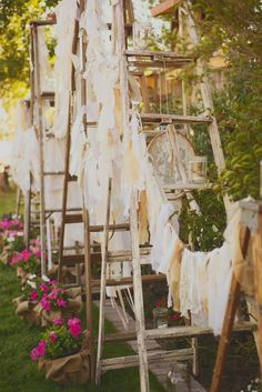 A collection of old ladders, handmade vintage fabric buntings, and embroidery hoops adorned with lace, pearls, and ribbons created for the backdrop for the receiving line. (Photo courtesy of http://www.staceybishop.com)