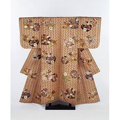 Robe, Kyoto, Japan, 19th century, Polychrome figured silk. The karaori is the basic outer robe worn by a Noh actor in female roles and the predominant red colour of the robe indicates the character a young woman. The robe is decorated with roundels of chrysanthemums, peonies and irises in coloured silks on a gold thread lattice pattern over a woven red silk ground