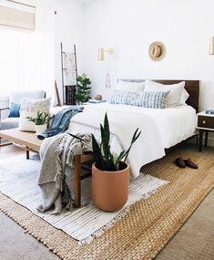 Pareti bianche, mobili vintage, tappeti sovrapposti e piante grasse per questa camera da letto dal mood boho-chic.