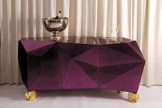 The Diamond Sideboard shown here takes on the shape of a multi-faceted jewel covered in a silver leaf finish over which layers of translucent amethyst high gloss varnish are applied. Faceted doors open to a gold leaf interior containing shelving and two drawers. The lion's head feet carved from mahogany provide gilded supports.