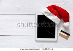 Christmas online shopping background. Tablet screen in santa hat top view on white wood with copy space and gold credit card near. Electronic devices, internet commerce on winter holidays concept