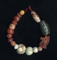 Seventeen beads and amulets of various materials and shapes - 750BC-300BC.