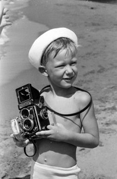 Prince Philippe of Belgium with camera on a beach in 1965