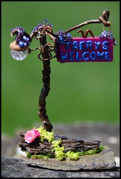 """Miniature Faery Garden """"Faerys Welcome"""" sign adorned with a street lamp to illuminate at night. I created this one with the obvious twigs, stones, moss, and the letters from alphabet soup noodles."""