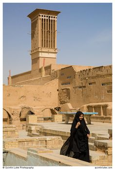 A woman passes in front of a  badgir, the Iranian term for wind tower. These chimney-like structures, which project above the roof, expel warm air during the day and trap cooler breezes at night. Yazd.