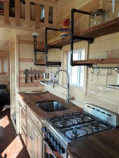 The kitchen is equipped with a refrigerator/freezer, a freestanding gas range, and upper shelving with pipe supports.