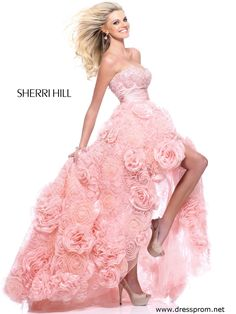 So elegant, romantic and dreamy prom dress for the girl that adores rosettes. Sherri Hill 21170 features a flirty hi-low skirt decked out in different sizes of sweet rosettes including its sweep train. Similar roses created with beadwork and pearls embellish the strapless slightly curved neckline bodice and a finely shirred satin sash surrounds the empire waistline. Purchase this sweet party gown 2014 in Light Pink or Ivory. Glamorous high heels with sassy front rosette are affordable at…