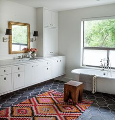 Creative Ideas For A Bathroom Makeover: Forgo the typical tiny floor tile in favor of something with a bit more heft, like this Hacienda tile from Ann Sacks. Paired with crisp white walls and cabinetry, the curvy tile looks rich and warm.