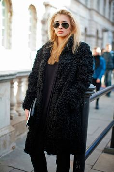 Street style look all black com fluffy coat preto, blusa calça e óculos estilo aviador.