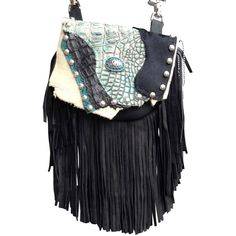 "BLACK SEAS MARTY - super soft, made of black deerskin with a 7"" black deerskin fringe. The flap features hair-on-hide calf, genuine alligator and blue-green printed leather. The centerpiece is a silver oval with sparkling blue stones. The combination is dramatic. Etched silver metal studs decorate the flap border.  Wear bag clipped to belt loops for hands-free carrying of your essentials. Interior includes a leather strap. Add the strap when you want a completely different look."