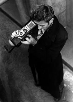black and white photo of james dean looking into a camera viewfinder.