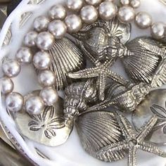 display silver starfish and shells in bowl
