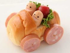 two hot dog kids sitting in salad seats riding in a roll car with ham wheels!.......great for the kids' table if they don't eat with the grownups.....