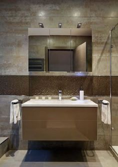 Ensuite bathrooms, the basin, truffle-coloured glossy vanity unit and mirrors are all from Keuco