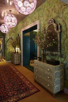 A chinoiserie-inspired wall panel by de Gournay enlivens a staircase and landing, whose decor was devised by Kati Curtis.