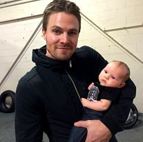 Stephen Amell holding a freaking baby. He's doing this on purpose.