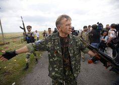 This photo shows the Pro Separatists troops clearing a huge crowd gathering in front of the MH 17 crash site.