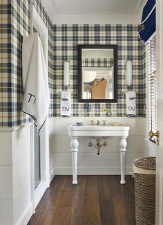 Boy's bathroom boasts upper walls clad in yellow and blue tartan wallpaper and lower walls clad in shiplap trim lined with a Parisian pedestal sink as well as a vintage glass shelf and framed medicine cabinet atop a wide plank floor.
