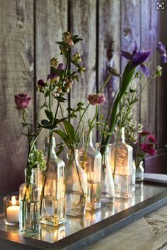 this floral arrangement in vintage bottles with tea-light candles behind, would also look good with white flowers Ikebana, Tea Light Candles, Tea Lights, Candle Lighting, Deco Floral, Vintage Bottles, Antique Bottles, Bottles And Jars, Small Bottles