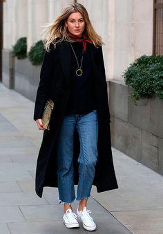 Camille Charriere anda na rua vestindo calça jeans reta, sobretudo preto, bandana no pescoço e converse all star