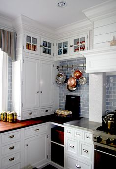 White cabinets & butcher block counter tops. love. (hate the pot rack though)