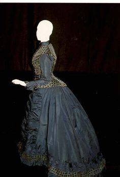 Day dress, Pingat, 1870s. Midnight blue faille and blue and brown silk cut velvet. Fitted, boned jacket--top has high neck, front button closure, long narrow sleeves and an attached cumberbund. Long skirt is ruched in center front and in back has a large bustle and train.