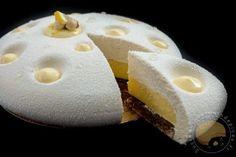 Entremets composé d'un biscuit moelleux aux amandes, d'un croustillant au praliné, d'une crème de citron onctueuse et d'une ganache montée au chocolat blanc et à la pâte de noisettes. Il a été réalisé dans le moule Luna de la marque Silikomart.