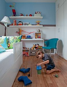 O quarto de Thomaz, 4 anos, tem tons de azul e marrom. Pequeno, tem espaço para a casa, uma escrivaninha e um guarda-roupa. As prateleiras ajudam a organizar os brinquedos. Projeto do arquiteto Nelson Kabarite