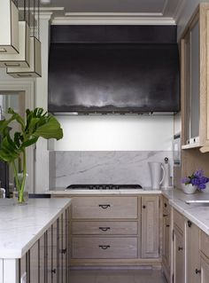 kitchen with light (pickled?) oak cabinets and marble counters. Zinc hood?