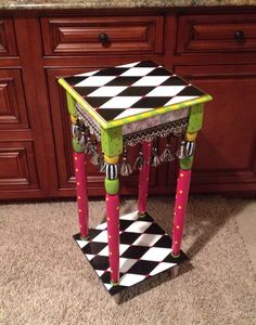 This adorable side table is hand painted in shades of pink, black, white, green, yellow and gold. Add a plant, flowers,