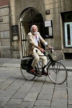 I like the tattoo on the left arm, the blue pocket square, the linen sport jacket, the pushed-up sleeves, all the bags and racks on his bike and the white beard, but I love the brown dress shoes.