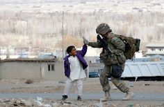 A U.S. Army soldier exchanges a high five with an Afghan boy during a patrol in Pul-e Alam, a town in Logar province, eastern Afghanistan, Nov. 28, 2011.