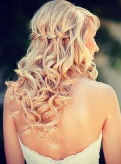 Turn your wedding day look up a notch with a waterfall braid incorporated in your curly locks.