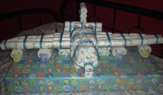 Homemade Diaper Cake: I used about 2 packs of diapers for about 120 diapers to complete this diaper cake.   I made a lay out of the wings and body out of card board and worked