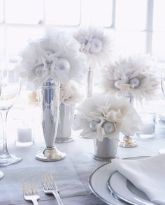 All-white is whimsical. These tissue paper flowers were arranged at different heights in silver trumpet vases and sparkling mint julep cups.