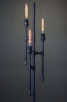 This floor lamp makes a statement by mixing the industrial style with gothic elements. Three 60 watt tube edison bulbs supply a warm ambient light (included with purchase). The fixture is artfully handmade using several different diameters of iron piping. Power is supplied by a retro style cloth covered cord with inline switch. Dimensions: Height - 68in Width - 11 in Depth - 11 in Specifications: (Standard) E26 Socket Black Vinyl Polarized Plugs NEMA 1-15P, 2-pole, non-grounding, rated 15...