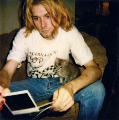Kurt Cobain looks at some polaroids while his kitten, Spina Bifida, looks on.