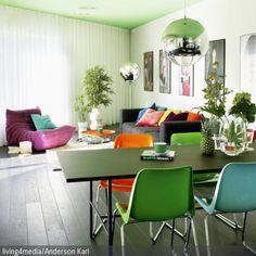 Das Zimmer erhält durch den schwarzen Tisch und die Kunststoffstühle im Retro-Look in Grün, Hellblau und Orange ein farbenfrohes 60er-Jahre-Flair. - mehr auf roomido.com