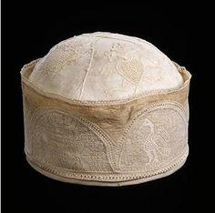 Bonnet de Charles Quint  Espagne, vers 1550 lin et broderie.    La petite taille de ce bonnet (O,18m de diamètre) nous renseigne sur son usage : il était très probablement destiné à servir de doublure à la couronne de l'empereur Charles-Quint, posée, et non enfoncée, sur sa tête.
