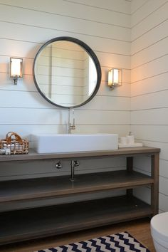Lonny via Design Chic. Love the planked walls, round mirror and wall sconces.