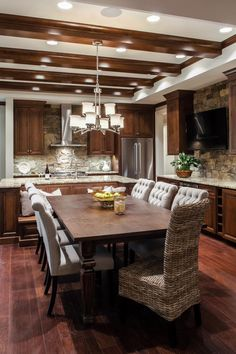 Custom wood cabinets and exposed beams combined with a stacked stone backsplash creates a cozy rustic feel in this elegant, transitional kitchen. A large dining table is surrounded by plenty of comfy chairs making it a great place to entertain.