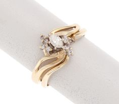A gold ring featuring several cuts and styles of diamonds in a swoopy base.