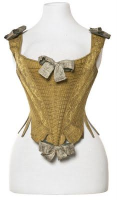 This Corps a' baleine, is dated 1735-1770, they are giving themeselves a wide range on this pair. Again the spade at center front and the spreading fingers. Decorative false lacing covers the center fronts. This lacing is not functional, but only for display. A beautiful gold damask is the fashion fabric and the stays are fully boned. Ignore the bows, the stylist put those on for the photos. The styling certainly suggests the earlier date.