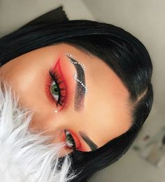 Red makeup with gems wrapping around the eyebrows