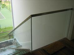 Guarda-corpo de escada feito em vidro e com perfil delicado de alumínio bronze.