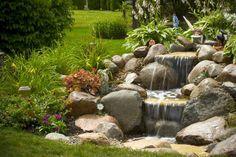 petite cascade de jardin de design original en pierres naturelles entourée de vivaces et de fleurs